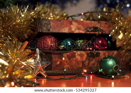Beautiful wooden box filled with Christmas ornaments and surrounded with decorations