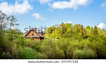 Beautiful wooden cottage somewhere in forest and blue sky above - stock photo