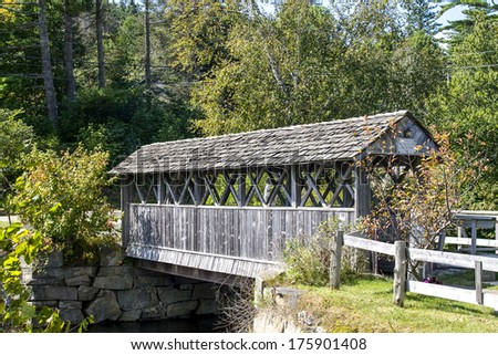 Beautiful wooden covered bridge in rural landscape - stock photo