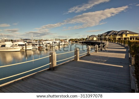 Beautiful wooden pedestrian pathway in front of marina full of luxurious boats - stock photo
