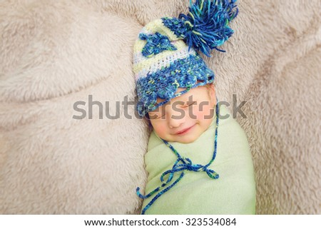 Beautiful wrapped newborn smiling baby boy in knitted hat sleeping on plaid. Copy space. - stock photo