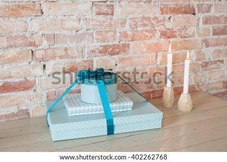 Beautiful wrapped presents on a wooden table, with candle lights, and brick wall in the background - stock photo