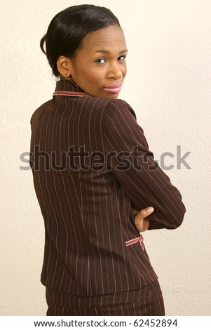 Beautiful 25 year old african american woman against office wall looking over shoulder. - stock photo