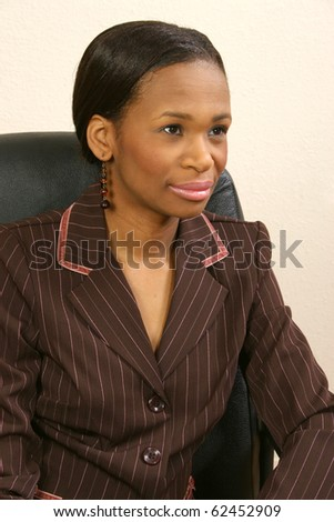 Beautiful 25 year old african american woman in suit sitting office chair. Looking away.