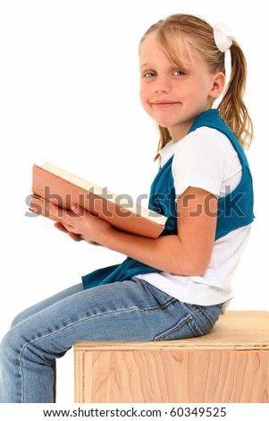 Beautiful 7 year old american girl sitting on wooden box with large book smiling over white background.