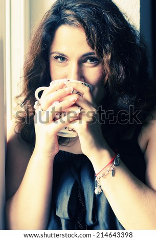 beautiful 35 years old woman holding cup of morning coffee - stock photo
