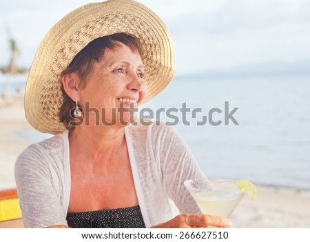 beautiful 50 years old woman in a hat with a cocktail in hand. Summer, vacation, holiday, active retired people - stock photo