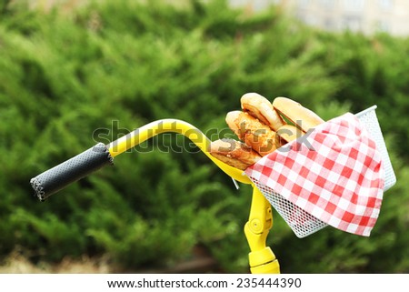 Beautiful yellow bicycle in park with tasty bread in basket - stock photo
