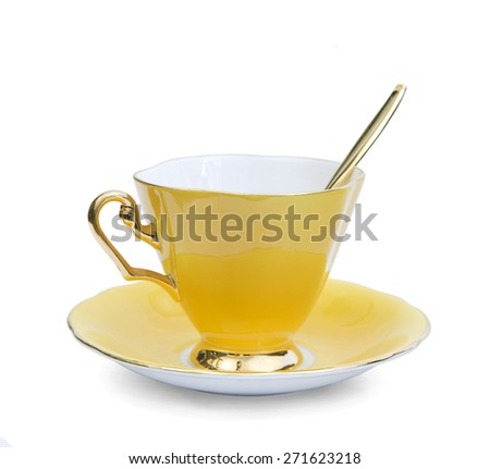 beautiful yellow empty coffee cup with gold handle and spoon - stock photo