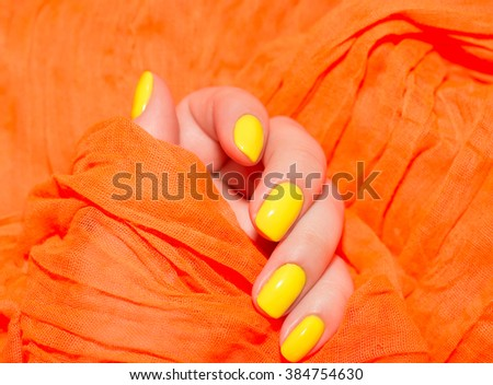 Beautiful yellow nails manicure. Light manicure in light on a white background. - stock photo