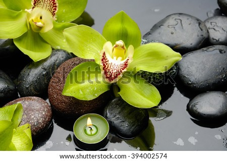 Beautiful yellow orchid with,candle and therapy stones