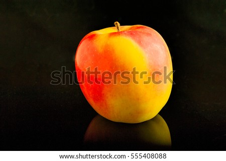 Beautiful yellow-red apple  lie on a black glass table with reflection