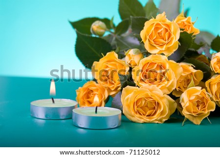 Beautiful yellow roses and candles on a green background - stock photo
