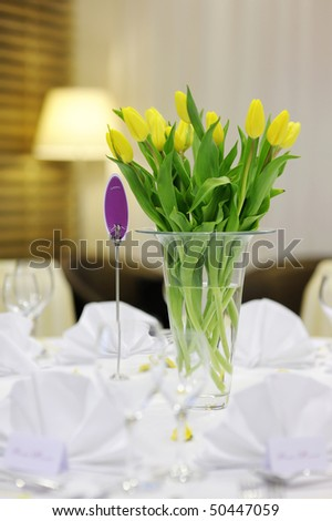 Beautiful yellow tulips on a white festive table - stock photo