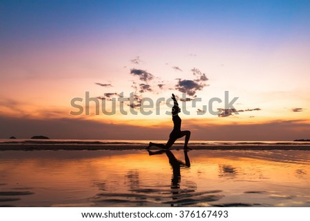 beautiful yoga exercise on the beach at sunset, fitness background with copyspace