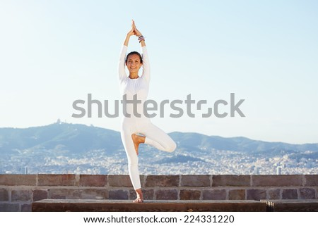 Beautiful yoga with amazing view of city on background, pretty healthy woman with perfect body stand in one of yoga pose and looking to the camera with smile, feeling neatly with yoga - stock photo
