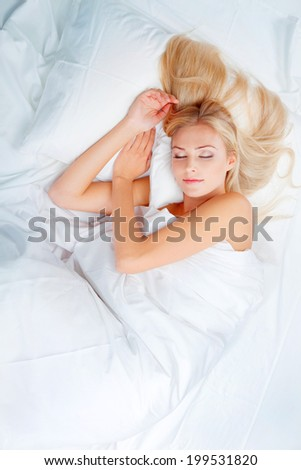 Beautiful yong blonde sleeps in white bedroom - stock photo