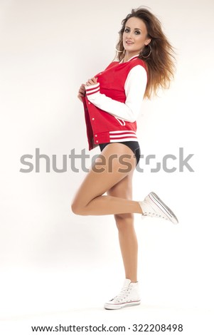 Beautiful young adult active sexy sensuality and attractive cheerleader girl in a red uniform baseball jacket with long brunette hair Isolated on a white background - stock photo