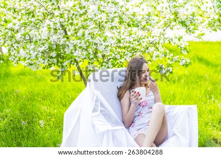 beautiful young adult caucasian girl sitting with cup of coffee and white sweat in park cafe on green grass and blooming tree background Slim female sit on white armchair Copy space for inscription - stock photo