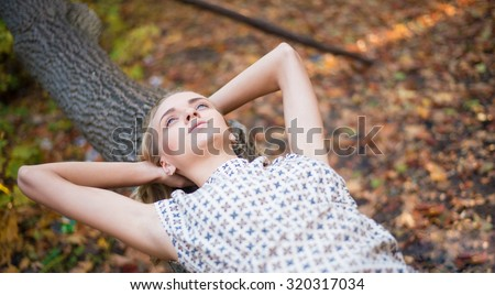 Beautiful young adult girl wearing luxury dress lying on a fallen tree trunk and relaxing deep into the forest Cute woman enjoy nice day in autumn park Empty copy space for inscription  - stock photo