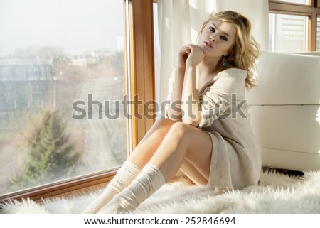 beautiful young adult slim sexy sensuality and attractive pretty blonde woman in brown sweater and white socks on white fur carpet against the morning sunlight window in luxury style apartment - stock photo