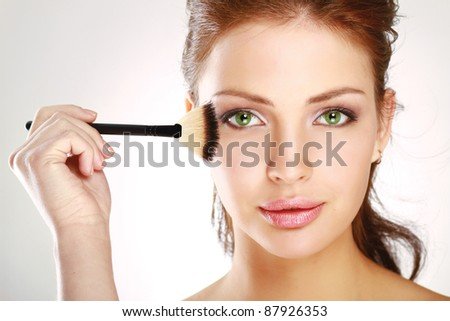 Beautiful young adult woman applying cosmetic paint brush - stock photo