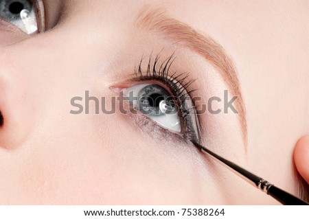 Beautiful young adult woman applying cosmetic paint brush - close-up portrait of eye shadow zone - stock photo