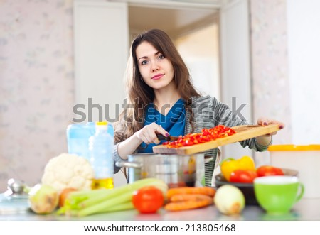 beautiful young adult woman cooking veggie lunch with vegetables in  kitchen  at home - stock photo