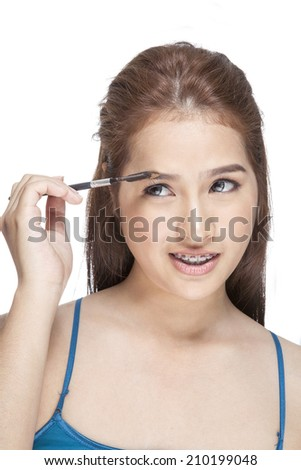 Beautiful young adult woman draw beauty shape of eyebrows using cosmetic brush - stock photo
