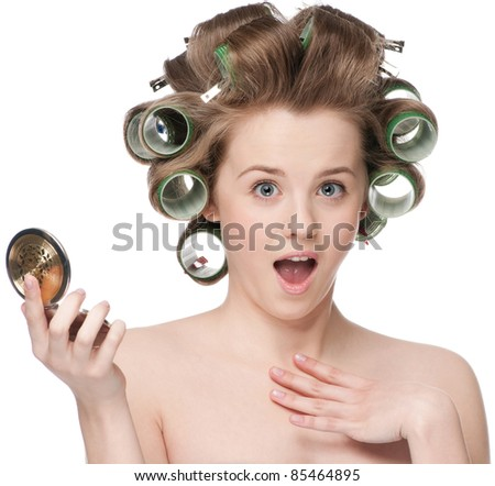 Beautiful young adult woman in hair roller looking in mirror - close-up portrait - stock photo