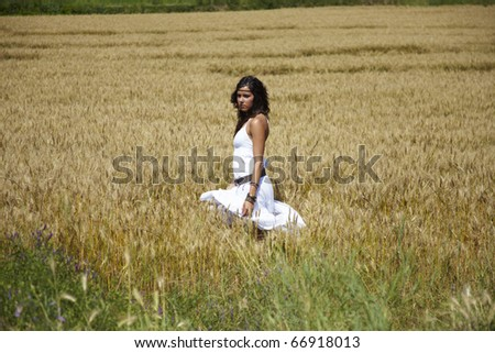 Beautiful young adult woman standing on a wheat field in the middle of a hot summer afternoon. Nice colors, pretty girl and lovely bright day. She dresses in white and relaxes outdoors. - stock photo