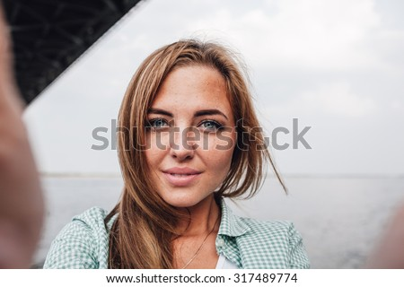 beautiful young adult woman taking picture of herself, selfie. - stock photo