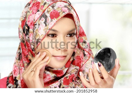 beautiful young adult woman with cotton pad. applying face powder - stock photo