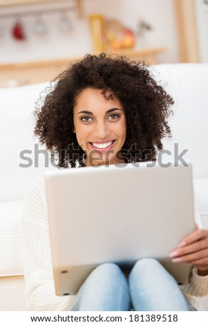 Beautiful young African American student sitting on the floor in her living room with her laptop on her knees looking at the camera with a lovely friendly smile - stock photo