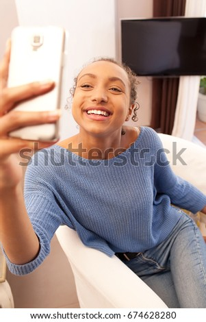 Beautiful young african american woman holding smart phone taking selfies photos, networking smiling with fun expression. Black teenager using technology at home, entertainment recreation lifestyle.