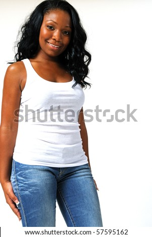 Beautiful young African American woman in white tank top and blue jeans - smiling - stock photo