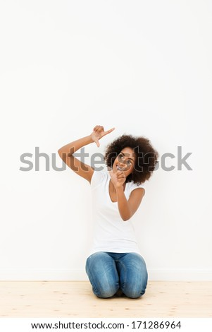 Beautiful young African American woman kneeling on the hardwood floor of her new apartment visualizing her new decor by making a frame with her fingers - stock photo