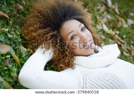 Beautiful young African American woman smiling with afro hairstyle and green eyes wearing white winter dress laying on the grass of an urban park - stock photo