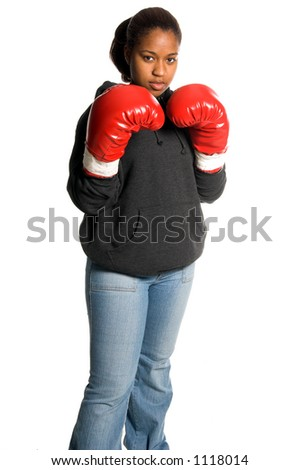 Beautiful young African American woman throwing a punch with boxing gloves