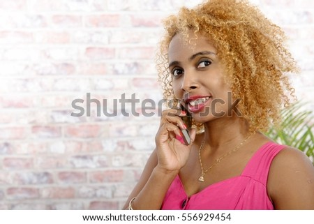 Beautiful young african american woman using mobile phone, at home
