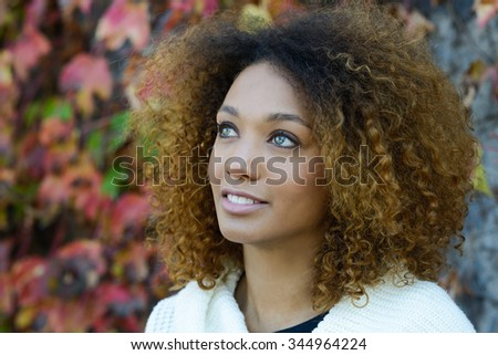 Beautiful young African American woman with afro hairstyle and green eyes wearing white winter dress with autumn leaves in the background.