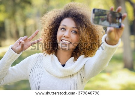 Beautiful young African American woman with afro hairstyle and green eyes wearing white winter dress. Beautiful Girl selfie in the park with a smartphone. - stock photo