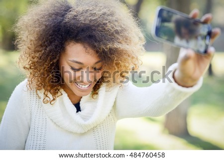 Beautiful young African American woman with afro hairstyle and green eyes wearing white winter dress. Beautiful Girl selfie in the park with a smartphone.