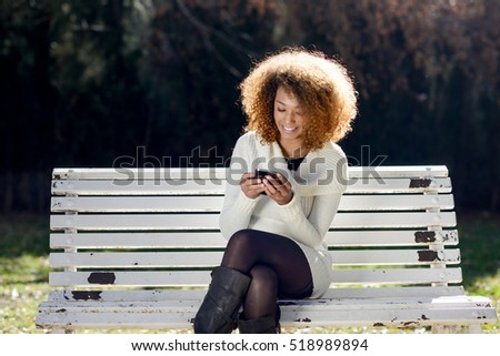 Beautiful young African American woman with afro hairstyle wearing white winter dress. Beautiful Girl sitting in the park with a smartphone.
