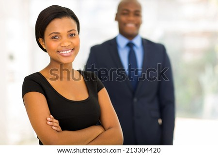 beautiful young african businesswoman standing in front of her colleague - stock photo