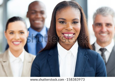 beautiful young african businesswoman with colleagues on background
