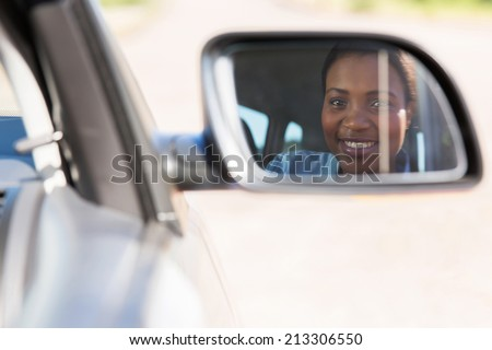 beautiful young african female driver looking at side mirror - stock photo