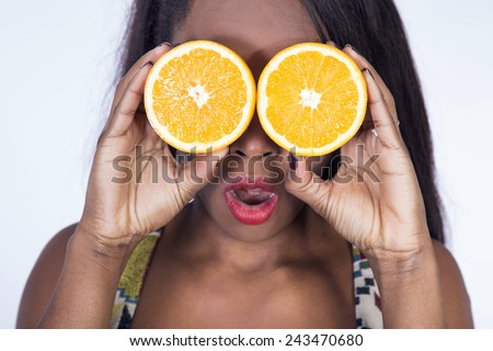 beautiful young African girl eating an orange - stock photo