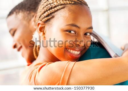 beautiful young african girl hugging her boyfriend - stock photo