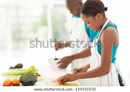 beautiful young african woman chopping tomato in kitchen - stock photo